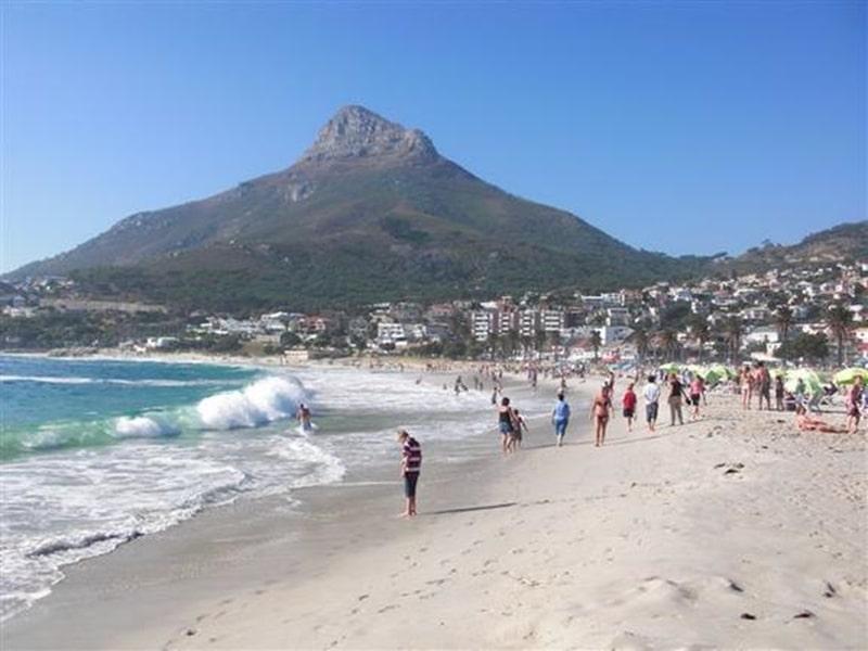 Südafrika, Camps Bay Reisende am Strand im Hintergrund der Tafelberg