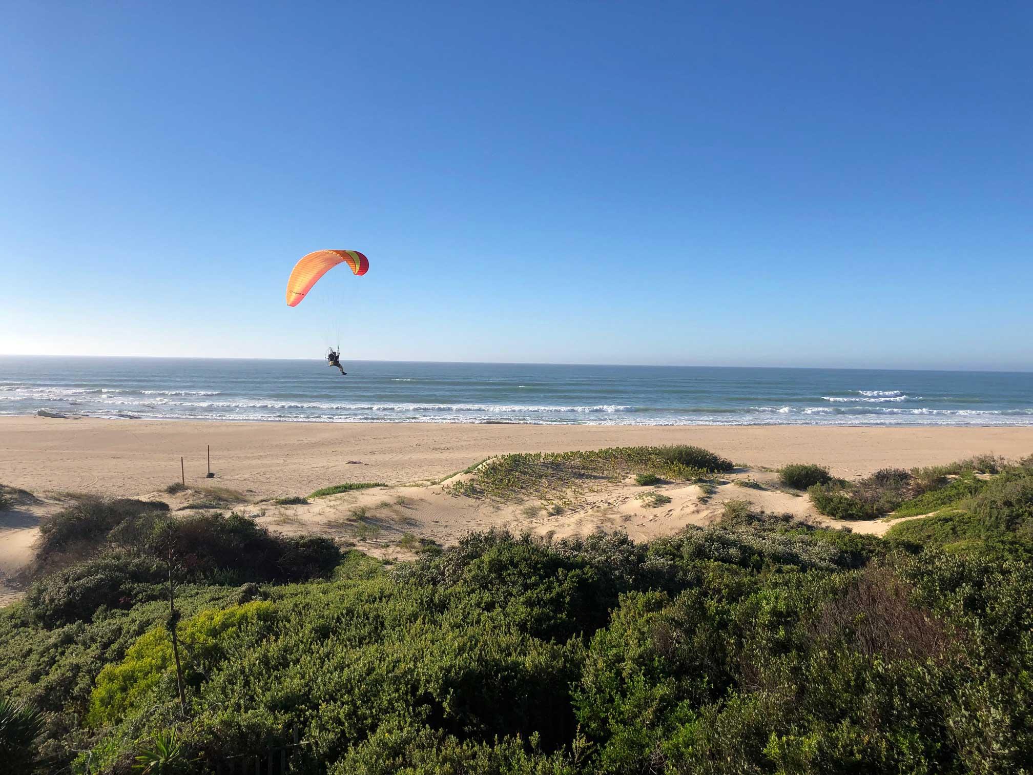 Ein Paraglider fliegt über Jeffresy Bay